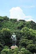 城山を背景に立つ西郷隆盛像