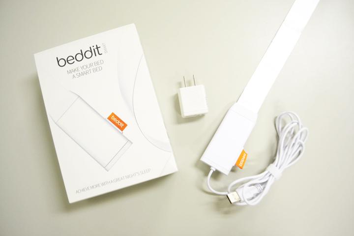 「Bedditスリープモニター」。厚さ約1mmの帯状のセンサーと電源アダプターがセットになっています。