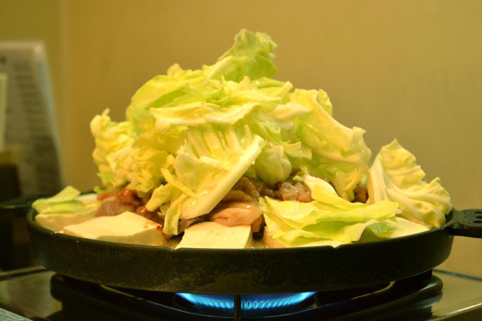鍋の中央にホルモン、縁に豆腐を並べて、その上からキャベツをどっさり。鍋に乗った状態で改めて見ると、ものすごいボリューム。
