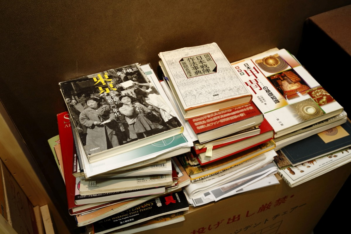 甲冑の資料や昭和の写真集が棚代わりのダンボールの上に山積みに。(撮影場所5)