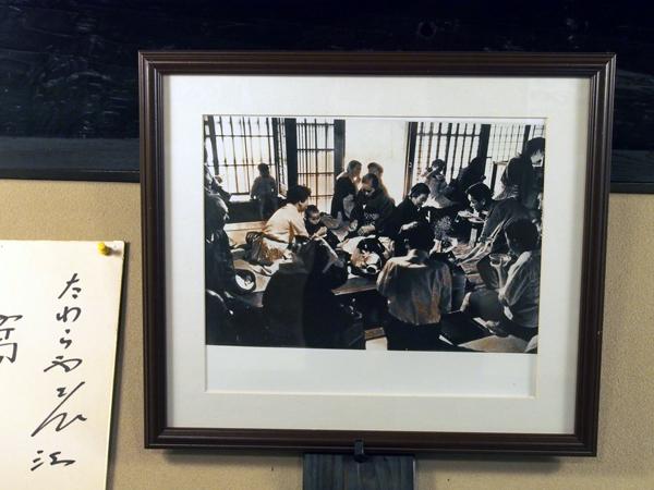 昭和時代の「たわらや」の写真。客はお盆にのせたうどんを、思い思いの場所に座って食べています。