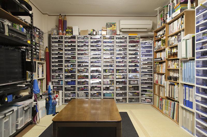 (2)壁一面を覆い尽くす、文具入りのケースの山! この部屋に移ってからケースの数が倍になったとか。