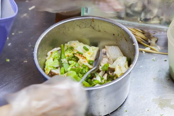超高速の包丁さばきで細かく刻まれた野菜は、一度塩味のスープに通され、ボウルの中でタレと和えます。